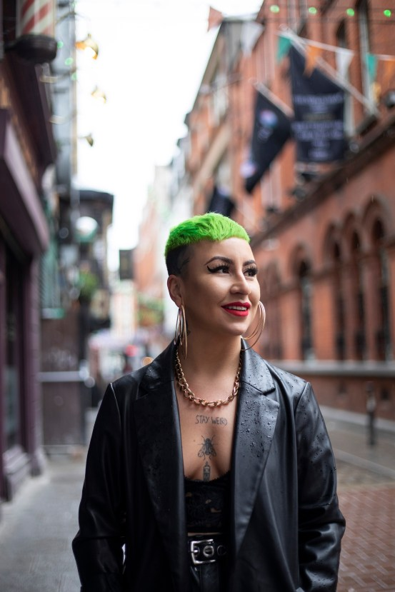 A young woman with green hair and tattoos looks into the distance