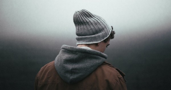 A young man wearing a beanie hat and coat outside seen from behind