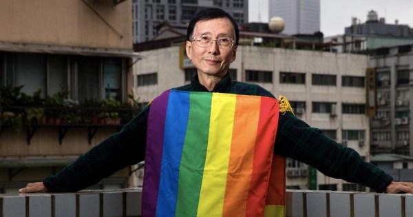 An older Asian man on a balcony draped in a rainbow flag