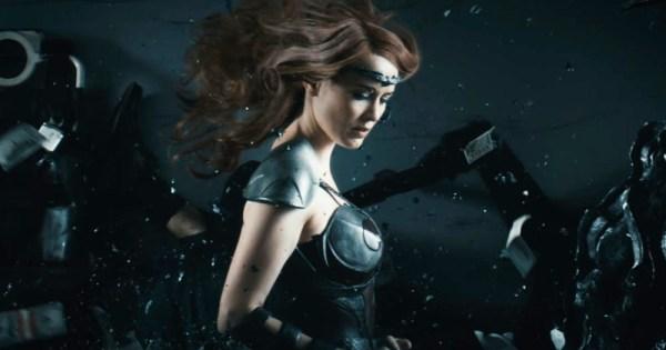 A female superhero walks through a battle