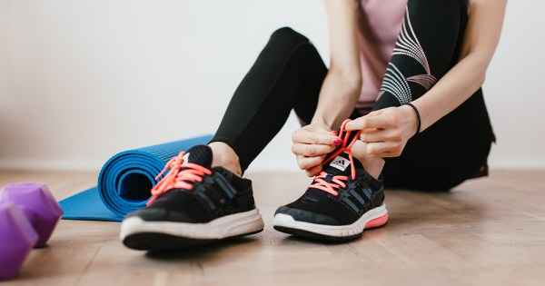 A woman ties the laces of her runners