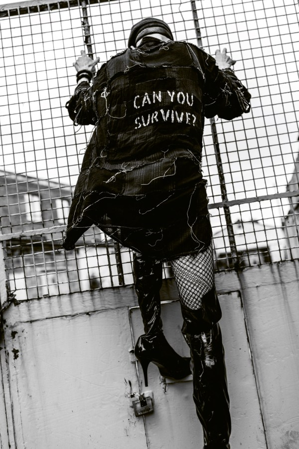 """Drag queen Veda from behind holding during a lockdown photoshoot. She is wearing a jacket that reads """"Can you survive""""?"""