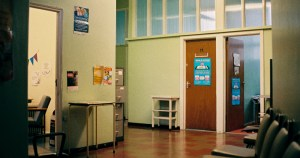 inside the GHN Baggot St waiting area a door with a poster in a hospital like corridor