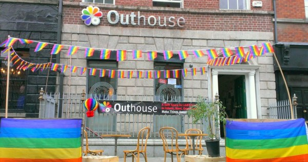 exterior of Outhouse decorated in pride flags
