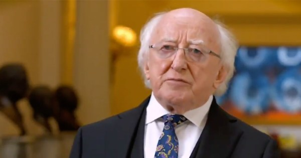 An older man wearing glasses speaks to a camera