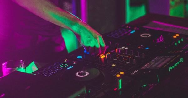 A DJ's hands at a mixing desk