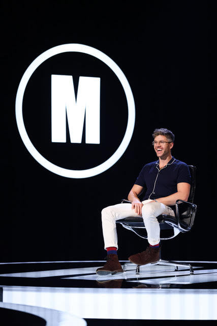 darren kennedy sitting on the black chair on the mastermind stage