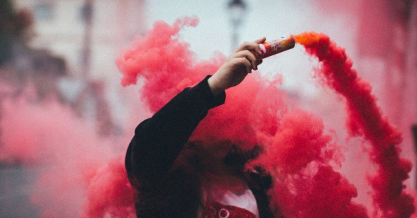 Far Right a person holds a smoke bomb which is billowing red smoke as they walk down a street