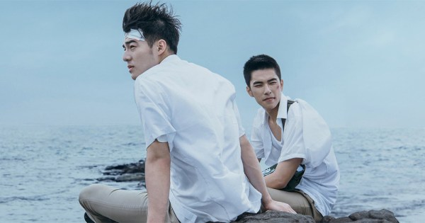Two young men sit on a windy beach