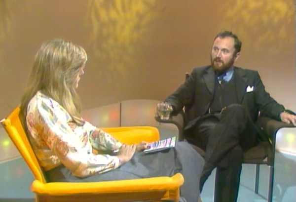 A man and woman sit in a TV studio
