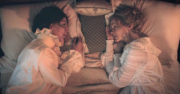 a Still image from Lesbian Period drama on SNL with two women lying in bed opposite each other in old fashioned nightdresses in candlelight