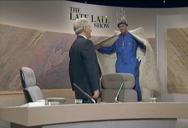 From RTÉ queer Archives: A man in a large fur coat and a crown greets another on the set of a TV studio