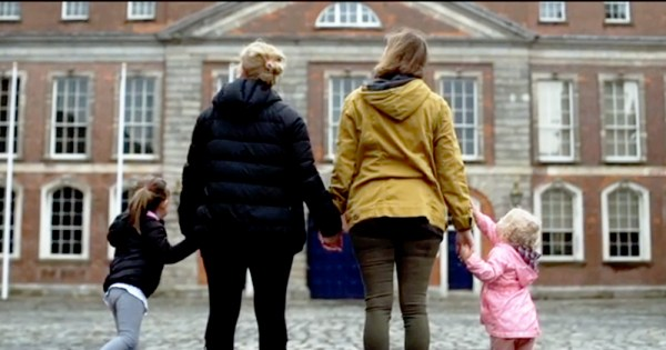 Two women holding two little girls' hands outside a building