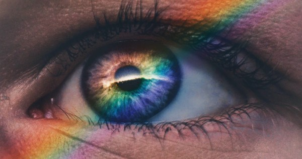An eye with a rainbow reflected in it
