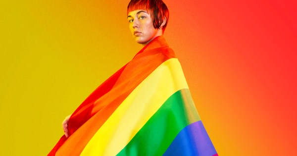 A girl wrapped in a rainbow flag