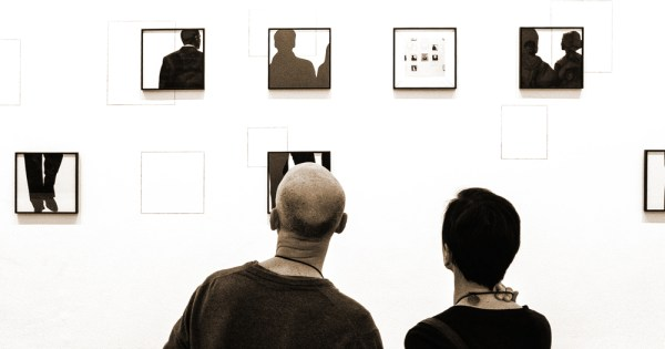 Two people looking at small framed images in a gallery
