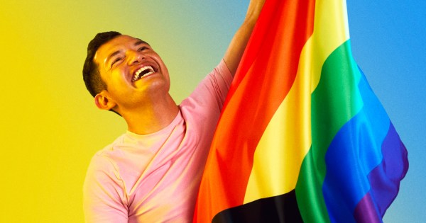 A man laughing while holding a rainbow flag. In this piece, Jorge shares his coming out journey