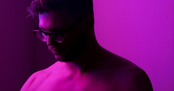 A shirtless man under pink lighting bows his head