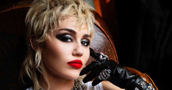 A close-up portrait style photo of Miley Cyrus, with blonde hair, a smokey-eye makeup look, and red lipstick. Cyrus is wearing black leather gloves and she is sitting on a brown leather seat.