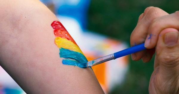 Neuro Pride will launch in August: In the photo a close up of a hand painting a rainbow on someone's arm.