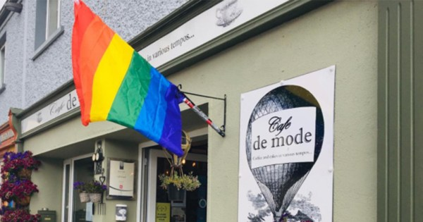 A rainbow flag hanging on the outside wall of a cafe