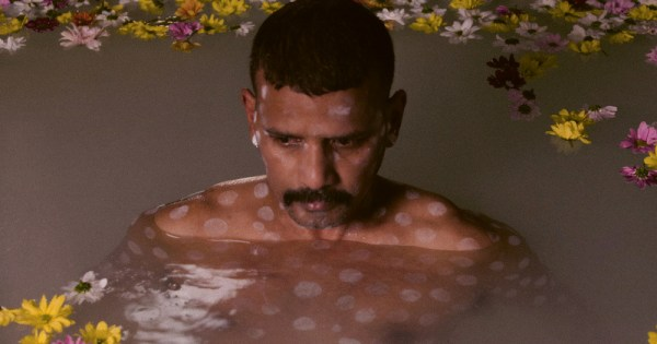 Asian man floating in water with flowers. In this piece, Pradeep Mahadeshwar talks about sexual racism