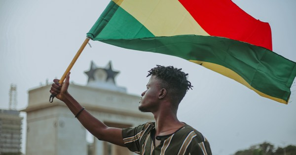 A photo of a man flying the Ghanaian flag. There is a government building in the background.