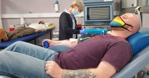 Two men giving blood in a clinic while nurse stands by