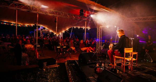 SoFFT Nights promo shot: A man playing an accordion onstage in a tent with people watching