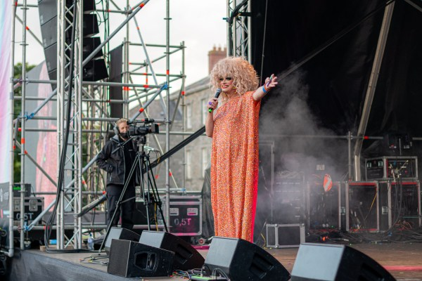 Panti hosting the main stage of the Block Party wearing an orange kaftan with her arms aloft