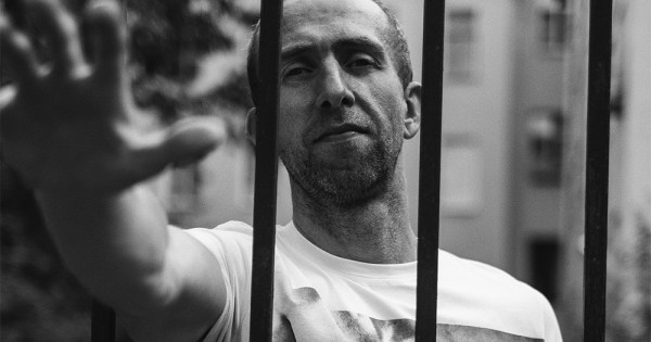 A man reaching out between the bars of a gate