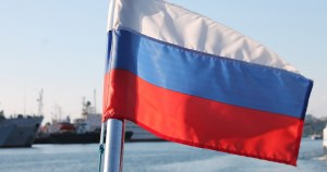 Close-up of the Russian flag, boats can be seen in the background. Russia has proposed to label LGBTQ+ groups as extremist.