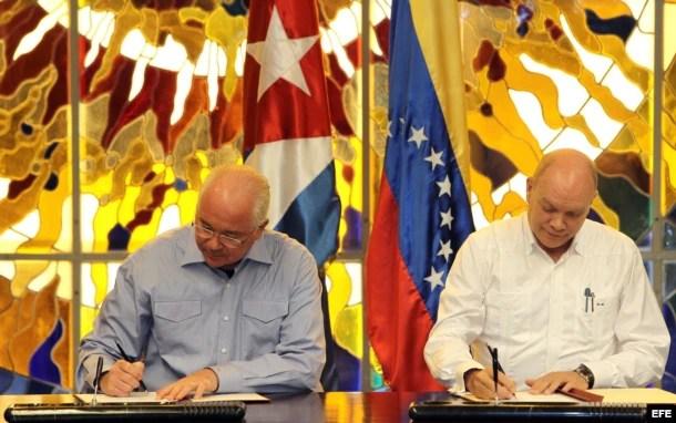El vicepresidente de Venezuela Rafael Ramírez (i), y el ministro cubano para el Comercio Exterior y la Inversión Extranjera, Rodrigo Malmierca (d), firman un acuerdo de cooperación.