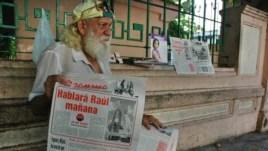 """Un hombre sostiene un ejemplar del diario """"Granma"""", órgano oficial del Partido Comunista de Cuba."""