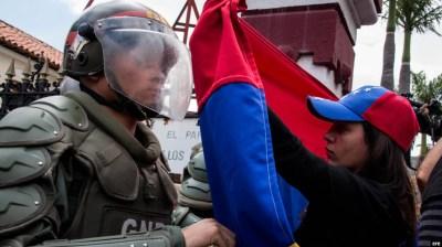 Una mujer sostiene una bandera de Venezuela frente a integrantes de la Guardia Nacional Bolivariana.