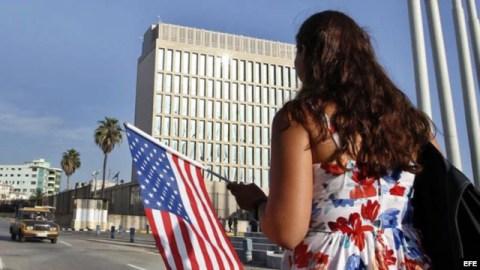 Una mujer camina con una bandera de EE.UU. frente a la embajada de ese país en La Habana