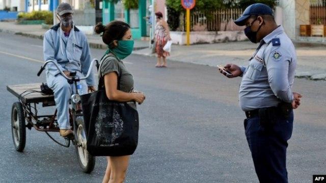 Un policía hace chequeos de peatones el sábado en el barrio El Carmelo, que el gobierno anunció inicialmente que iba a aislar y luego mantuvo abierto por temor a que se hiciera aún más difícil el acceso a provisiones, según reporta el diario 14ymedio (Foto: Yamil Lage/AFP).