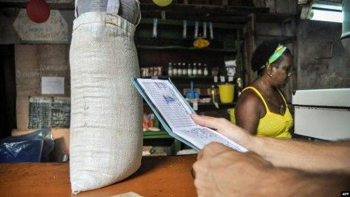 """Un hombre espera comida en una tienda mientras sostiene una """"libreta"""", una tarjeta de racionamiento que desde 1963 ha permitido a los cubanos comprar alimentos básicos. (Archivo)"""