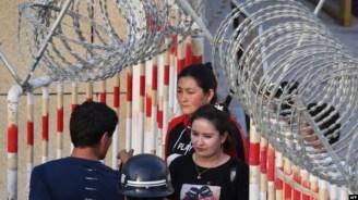 Uyghur women walk through a security checkpoint to enter a bazaar in Hotan, in China's Xinjiang Uyghur Autonomous Region.