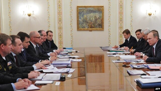 Russian President Vladimir Putin (right) speaks at a meeting with top officials on gas deliveries to Ukraine at his Novo-Ogaryovo state residence outside Moscow on April 10.