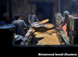 Men cook potatoes at a small traditional factory in preparation for Eid al-Fitr in Kabul on May 21.