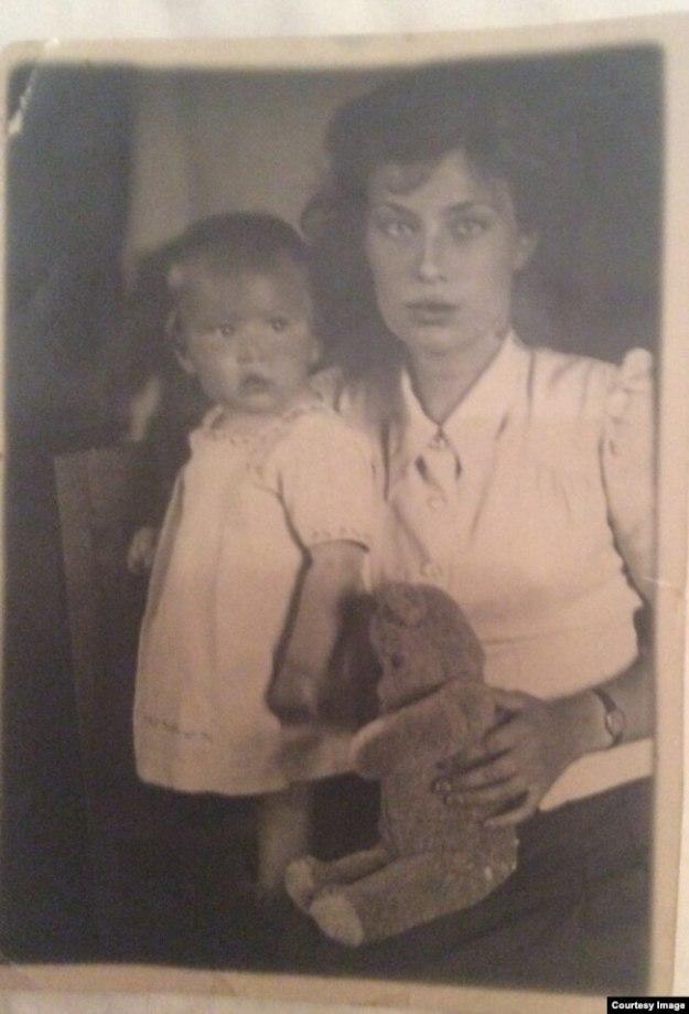"""""""Это первый официальный снимок меня с мамой. На мне – платье, в котором еще моему отцу делали обрезание, из крепкого белого сукна с голубой вышивкой. Когда я выросла, оно стало платьем моей куклы и позже было потеряно на тюремном этапе. Плюшевый мишка принадлежал фотографу. Моя мать умерла прошлой ночью в своей постели. Ей было 92""""."""