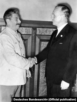 Генеральный секретарь ЦК ВКП(б) Иосиф Сталин пожимает руку министру иностранных дел нацистской Германии Йоахиму фон Риббентропу после подписания пакта Молотова – Риббентропа. Москва, 23 августа 1939 года