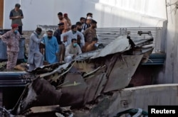 Karachi residents stand next to the debris of a passenger plane after it crashed near the city's airport on May 22.