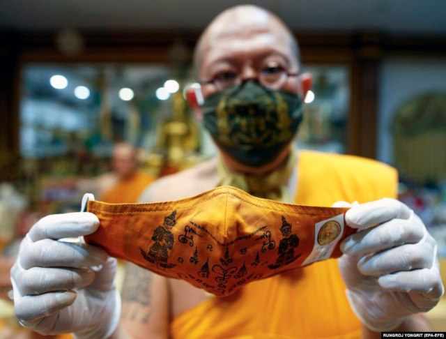 Thai Buddhist abbot monk Phra Kru Palad Sitthiwat holds a face mask he inscribed with spiritual incantations in Thailand's Nakhon Pathom Province on March 29.