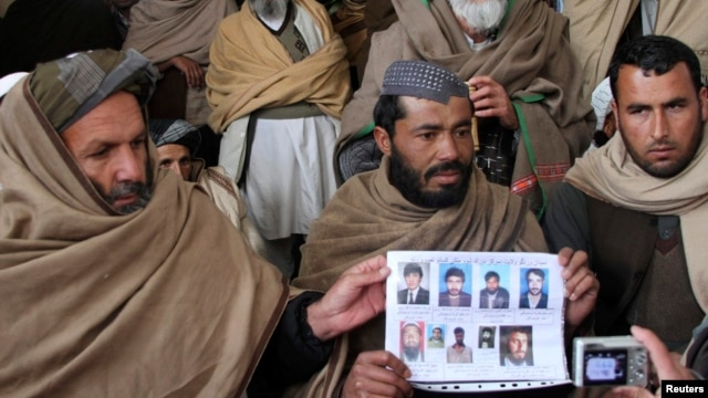 Afghan villagers show a picture of nine men during a protest last month against U.S. Special Forces accused of overseeing torture and killings in Wardak Province