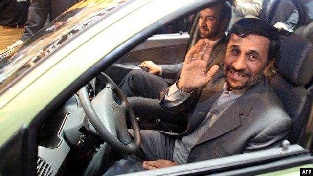 Iranian President Mahmud Ahmadinejad waves to the press as he sits in a car during an inaugural ceremony for Saipa group's All-Iranian Automobile production line, Miniator, in Tehran in December 2008.
