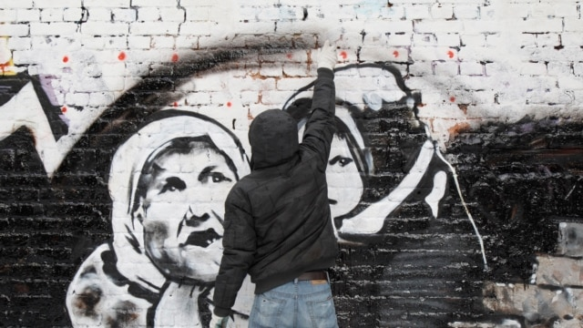 Russian street artist P183 paints a mural dedicated to forthcoming elections on a wall in central Moscow in February 2012.
