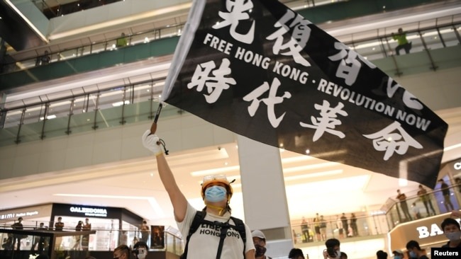 香港反送中抗议者在一个商场里挥舞旗帜。(2020年6月12日)