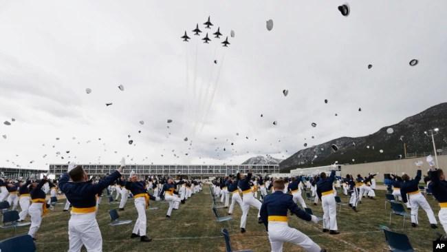 Los Thunderbirds de la Fuerza Aérea de EE.UU. sobrevuelan el campus de la Academia cuando los graduados de la clase 2020 lanzan sus gorras al aire para celebrar su promoción como oficiales. Sábado 18 de abril de 2020.